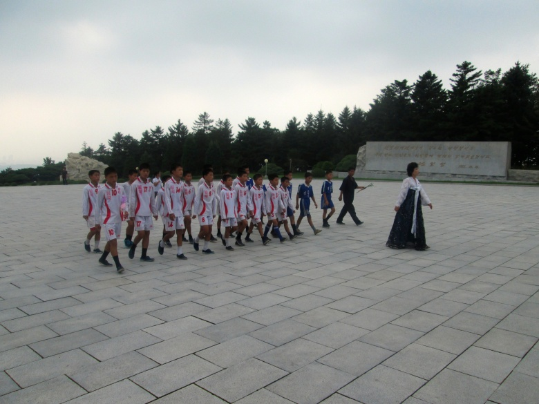 Teen soccer players on their way to pay respect to the Dear Leader.